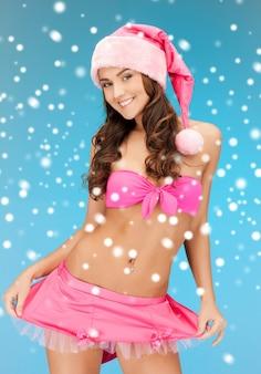 雪とランジェリーで陽気なサンタヘルパーの女の子の写真