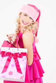 ショッピングバッグと陽気なサンタヘルパーの女の子の写真