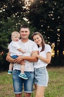 쾌활한 젊은 백인 여성과 남성의 사진은 손에 아이를 안고 미소를 짓고 기뻐합니다