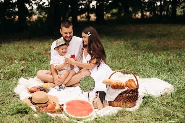 陽気な若い白人の女性と男性の写真は、子供を手に持って、笑顔で喜びます