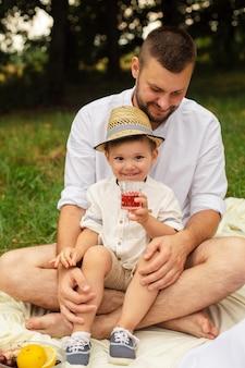 陽気な若い白人女性と男性の写真が子供を手に持って、笑顔で喜ぶ