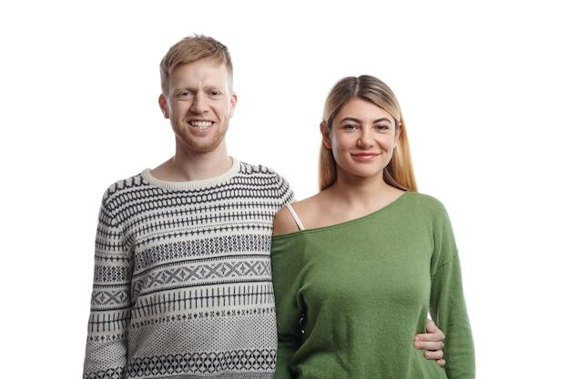 幸せな笑顔でポーズをとるスタイリッシュな服を着た陽気な若いヨーロッパのカップルの写真:彼女の腰で彼の金髪のガールフレンドを抱きしめるセーターのひげを生やした男。人、愛、人間関係