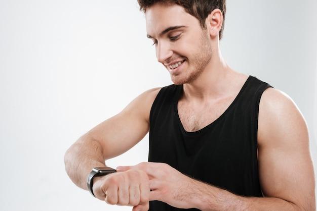 時計を見ている白い壁の上に立っている黒いtシャツを着た陽気な若い男の写真。