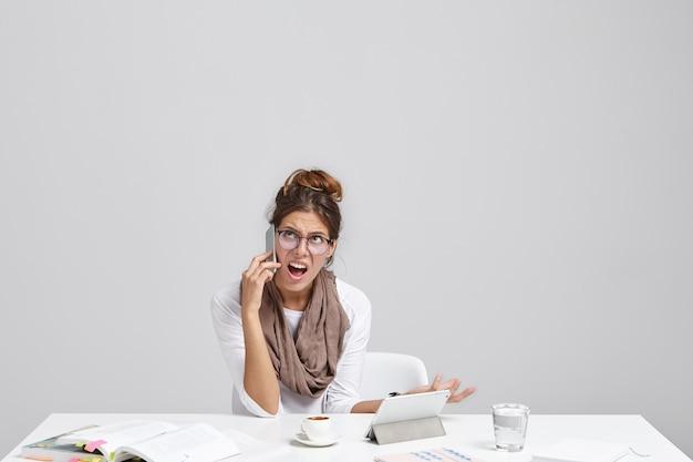 携帯電話で話している丸いメガネの無知な感情的な若い白人女性の写真