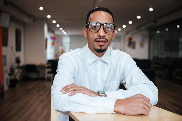 Изображение сосредоточенного бизнесмена в очках, сидящего за столом и смотрящего на фронт