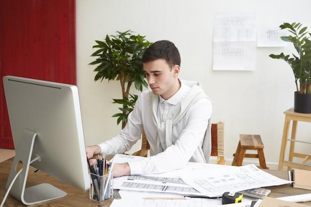 일반 컴퓨터를 사용하여 cad 시스템에서 작업하는 프로젝트 문서 및 도면과 함께 책상에 앉아 집중된 남성 건축가의 사진. 사람, 직업, 직업, 경력 및 기술 개념