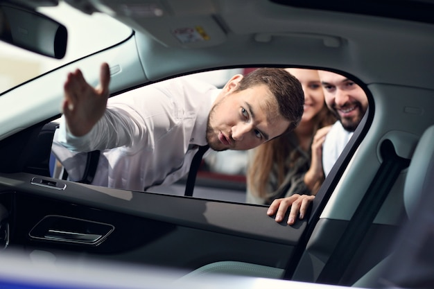 젊은 매력적인 소유자에게 모든 자동차 기능을 설명하는 자신감있는 젊은 세일즈맨의 사진