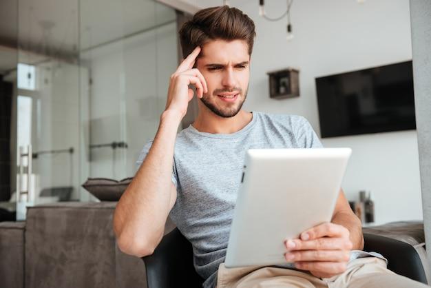 Фотография смущенного новобрачного в серой футболке, сидящего на стуле и держащего планшет, держась за голову рукой