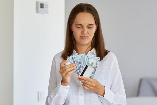 お金とクレジットカードを持って白いシャツを着て紙幣を見ている混乱した動揺した若い女性の写真は、夢の購入を買うのに十分なお金がありません。