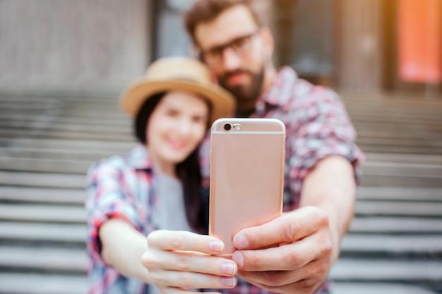 電話を一緒に保持しているカップルの写真と彼を見てください。彼らは笑います。観光客は階段の前に立っています。彼らはポーズします。