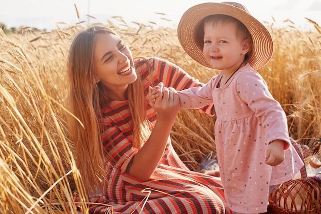 ピンクのスマートドレスを着ているかわいい子供、麦わら帽子、心から笑顔で母親と過ごす時間の写真。愛で彼女の娘を見て、笑って、手で彼女を握って甘いかわいいママ。