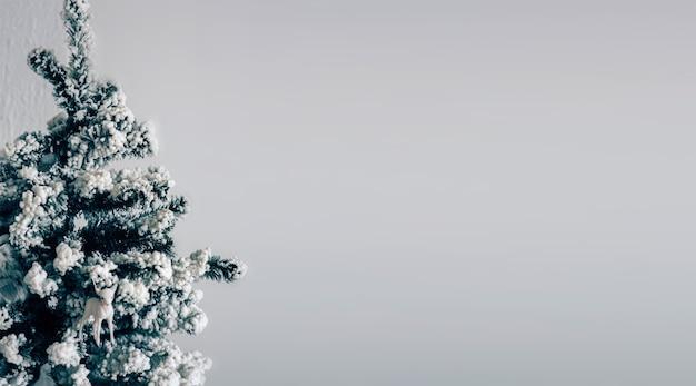 회색 배경 위에 절연 장식된 크리스마스 트리의 그림. 벽 앞에 서십시오. 사람이 없는 텅 빈 방. 연말연시 준비