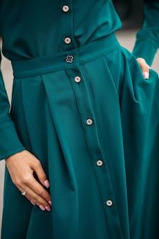 Изображение деталей длинного зеленого платья из плотной ткани с аккуратным пошивом и белыми пуговицами.