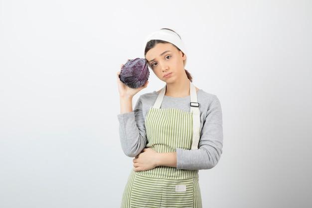 흰색에 보라색 양배추와 함께 포즈를 취하는 불쾌한 여자의 사진