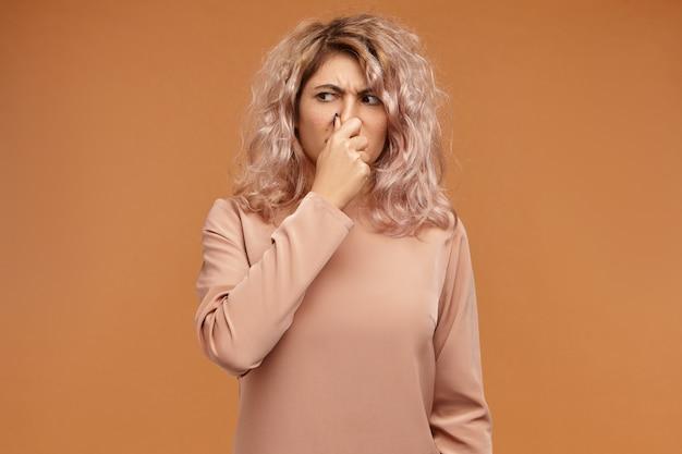 悪臭や悪臭のために鼻をつまんでいる、感情的に不快な若いヨーロッパ人女性の写真。スタイリッシュな10代の少女は汚れた靴下の臭いに耐えられない