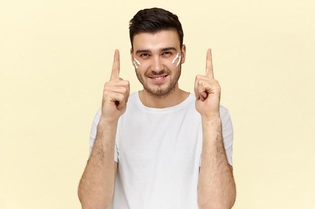 カメラに向かって微笑んで、前の指を上に向けて、頬に保湿剤を持っている感情的な大喜びの若い男の写真。指を上げるかわいい男、素晴らしいアイデアを持っています
