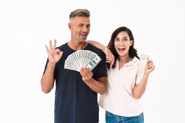 Изображение эмоциональной удивленной взрослой влюбленной пары, изолированной над белой стеной, держащей деньги и кредитную карту.