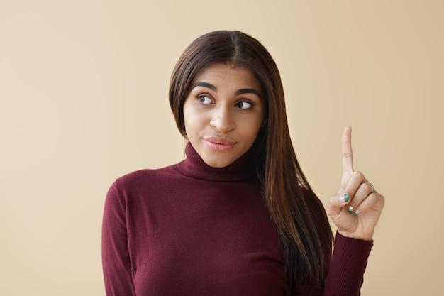 Картина эмоциональной молодой афро-американской женщины, глядя в сторону и указывая указательным пальцем вверх, имея яркую идею.