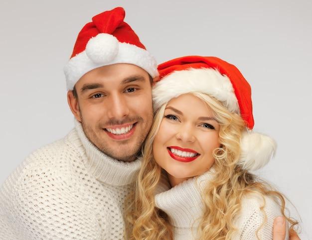 Картина семейной пары в свитерах и шляпах санта-клауса