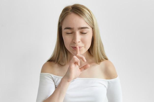 Фотография модной молодой женщины со светлыми волосами и веснушками, которая шепчет, закрывает глаза и держит указательный палец у рта, прося сохранить ее секрет. секретность и конфиденциальность информации