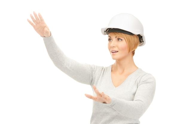 Изображение женщины-подрядчика в шлеме, работающей с чем-то воображаемым