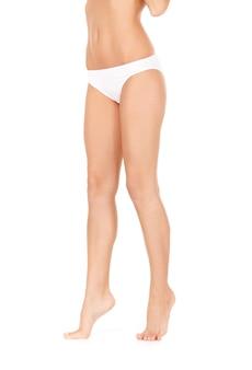 白いビキニのパンティーの女性の脚の写真