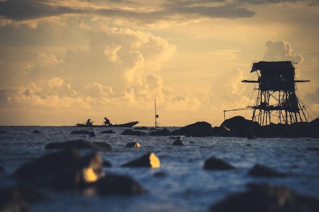 タイで一般的な朝の魚の海辺を探している漁師の写真