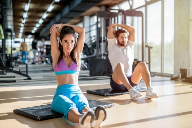 明るいジムに座って、トレーニング後に腕の筋肉を伸ばしてフィットハンサムなスポーティなカップルの写真。