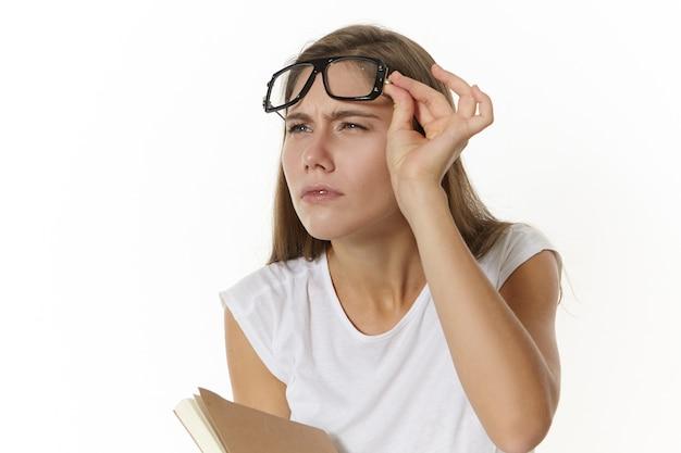 教科書を持って、眼鏡を外して目を細め、何かをはっきりと見ようとしている、集中力のある真面目な若い白人女性教師の写真。日記でポーズをとる眼鏡の学生の女の子