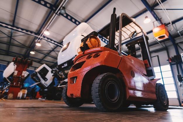 車の修理工場でのフォークリフトの写真。