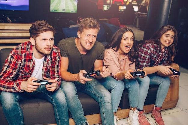 Изображение четырех человек, сидящих в одном ряду на диване в игровой комнате. они держат джойстики. люди играют в игру. они сосредоточены и счастливы.