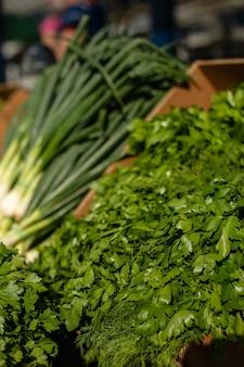 Изображение свежей зелени, овощей в картонной коробке на рынке