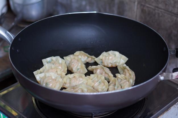 豚肉を鍋で焼いた餃子の炒め物の写真