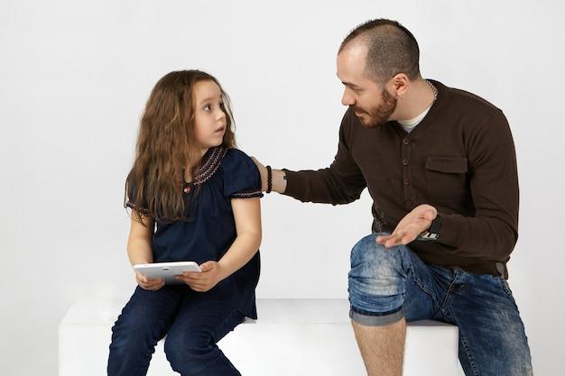 Фотография разочарованной девочки, расстроенной, когда ее молодой отец сказал ей выйти и поиграть в реальной жизни, вместо того, чтобы проводить слишком много времени в интернете и серфить в интернете на электронном планшете