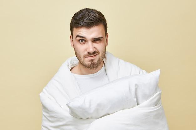 Фотография разочарованного молодого небритого мужчины, который чувствует себя напряженным, чтобы проснуться рано, завернутый в белое мягкое одеяло с подушкой в руках и сердитым выражением лица. постельные принадлежности