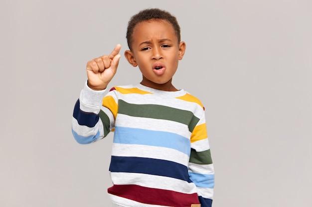 非常に小さなものを持っているかのように指でジェスチャーをしている、スタイリッシュなストライプのジャンパーを着た面白い暗い肌の男子生徒の写真。割引、セール、低価格