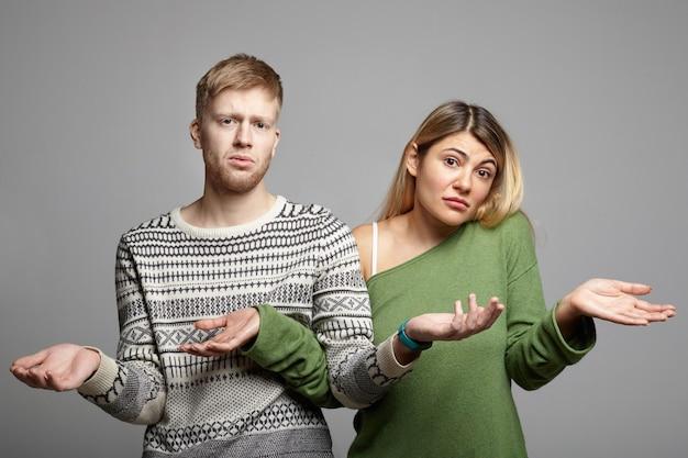 疑わしい無知な外見、開いた手のひらで肩をすくめる、迷子になっている、混乱と不確実性を探している面白い若いカップルの男性と女性の写真。ボディランゲージ