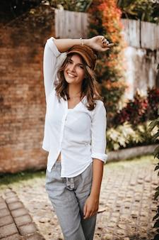 갈색 모자, 흰 블라우스, 린넨 바지를 입고 짧은 머리를 가진 소녀가 벽돌 건물과 덤불 공간에 손을 들었다.
