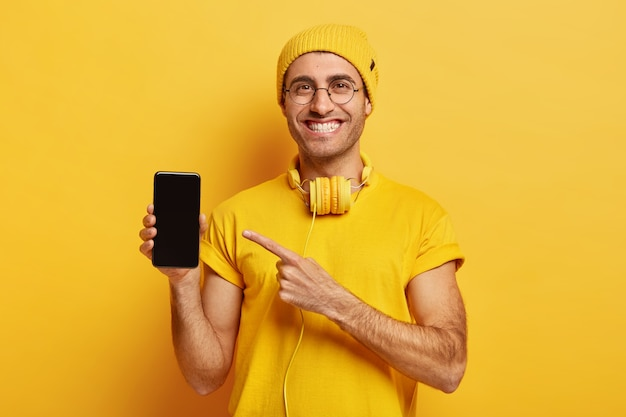 嬉しいハンサムな男の写真は、スマートフォンのディスプレイ、現代のガジェットのポイントを示しています