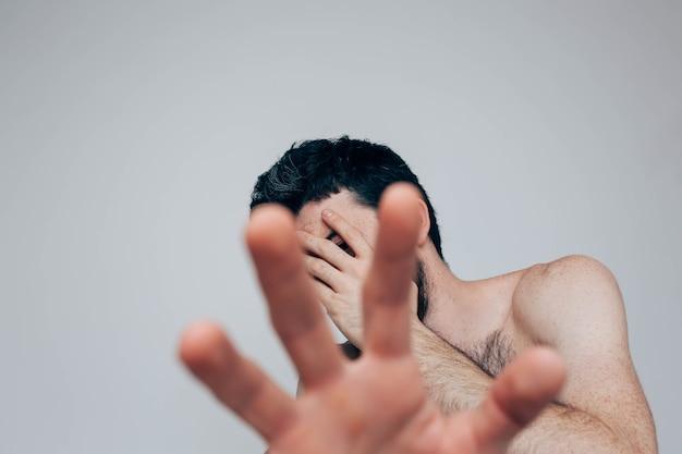 Изображение парня закройте лицо рукой и покажите другое. прячьтесь от болезней и психических расстройств. замешательство и беспокойство.