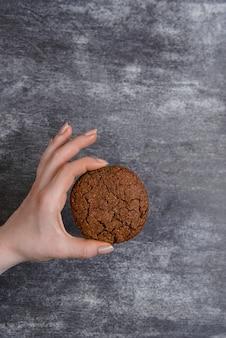 チョコレートクッキーを握る手の写真