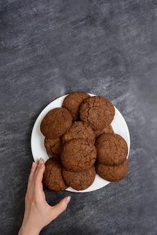 木の表面にチョコレートクッキーを置く手の写真