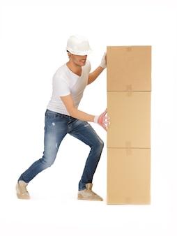 大きな箱を持つハンサムなビルダーの写真。