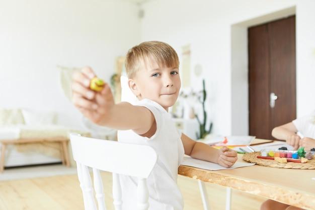 木製のテーブルに座って、黄色のモデルを示すモデリング粘土を使用してフィギュアを作る、色白の髪と青い目をしたハンサムな白人の男子生徒の写真。子供の顔に選択的に焦点を当てる