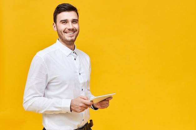 一般的なデジタルタブレットを保持し、オンラインアプリケーションを使用してゲームを楽しんで、広く笑っている白いシャツを着たハンサムな自信を持って若い男の写真。テクノロジー、エンターテインメント、ゲーム