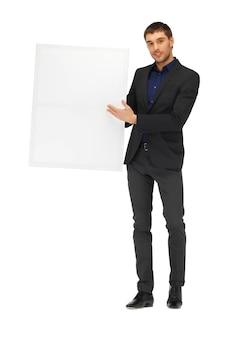 空白のボードとスーツを着たハンサムな男の写真。