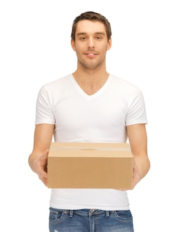 Изображение красивого мужчины с большой коробкой.