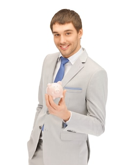 貯金箱を持つハンサムな男の写真