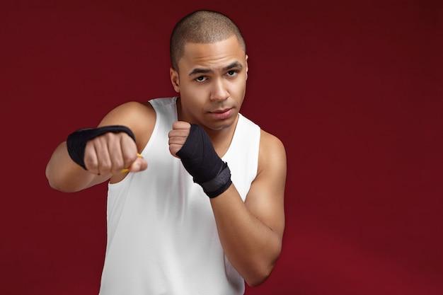 ボクシングの試合中に相手を殴る準備ができて、彼の前に拳を保ち、空白の壁でジムに立っている筋肉の腕を持つハンサムな強い運動の若い混血男ボクサーの写真