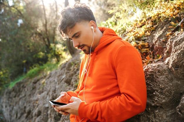 휴대 전화를 사용하여 이어폰으로 공원 듣는 음악 야외에서 잘 생긴 젊은 스포츠 피트니스 남자 주자의 그림.